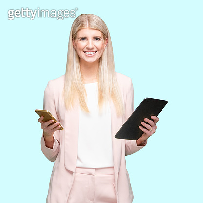 Caucasian female businesswoman standing in front of blue background wearing businesswear and using digital tablet