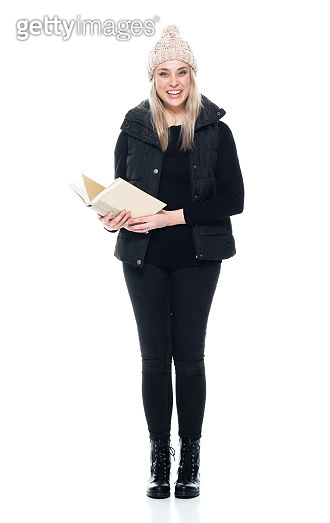 Caucasian female university student standing in front of white background wearing boot and holding textbook