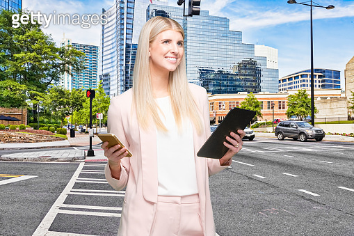Female businesswoman standing who is outdoors wearing businesswear and using touch screen
