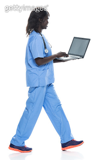 African ethnicity young women walking in front of white background wearing sports shoe and using computer