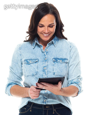 Caucasian mid adult women standing wearing pants and using digital tablet