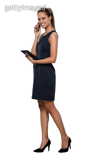 African ethnicity female businesswoman standing in front of white background in the office wearing dress and using touch screen
