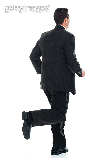 Caucasian young male manager running in front of white background wearing businesswear