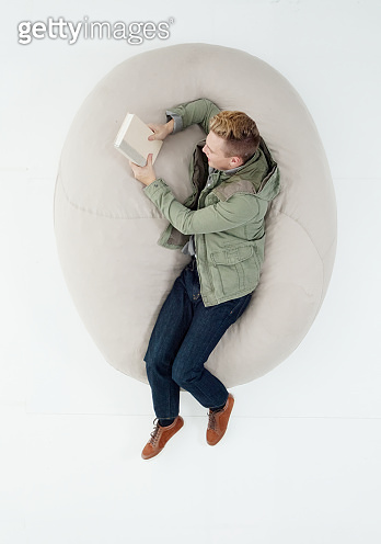 Caucasian teenage boys university student lying down in front of white background wearing pants and holding textbook
