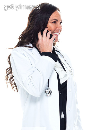 Caucasian young women doctor standing in front of white background wearing lab coat and using mobile phone