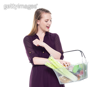 Caucasian teenage girls standing in front of white background wearing dress and holding shopping basket