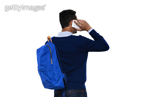 Generation z male standing in front of white background wearing backpack and using mobile phone