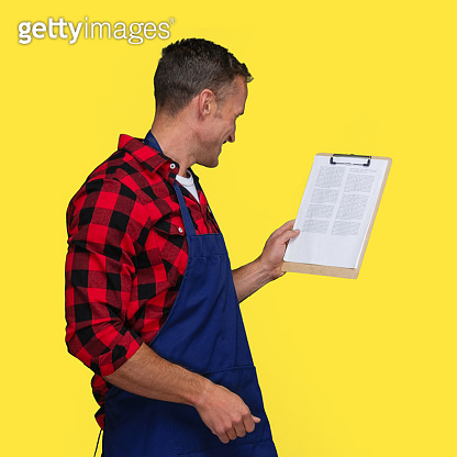 Caucasian male standing in front of yellow background wearing lumberjack shirt and holding to do list