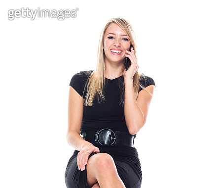 Caucasian young women business person resting in front of white background wearing businesswear and using mobile phone