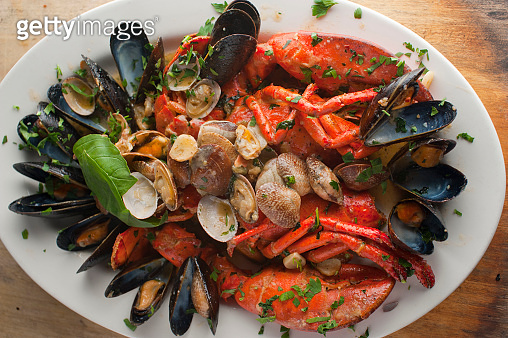 Lobster with Seafood stew or bouillabaisse. Classic Italian or French restaurant seafood entree. Made with lobster, scallops, mussels, razor clams, shrimp, octopus and squid sautéed in garlic, onions, butter and olive oil.