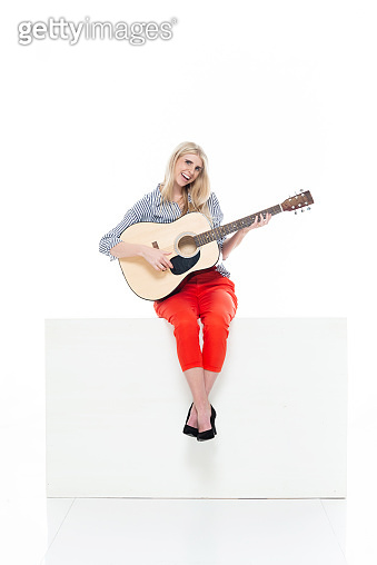 Caucasian female guitarist sitting in front of white background wearing business casual and holding acoustic guitar