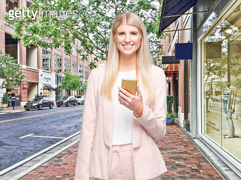 Young women businesswoman standing in the store who is outdoors wearing businesswear and using mobile phone