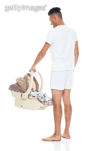 African ethnicity male standing in front of white background wearing boxer shorts and holding contract and using smart phone