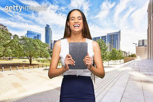 African-american ethnicity young women business person standing who is outdoors wearing business casual and using touch screen