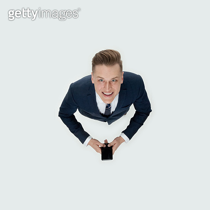 Caucasian young male business person standing in front of white background wearing businesswear and using mobile phone