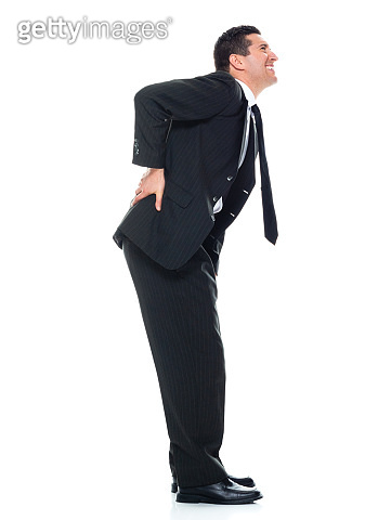 Caucasian young male business person bending over in front of white background wearing businesswear