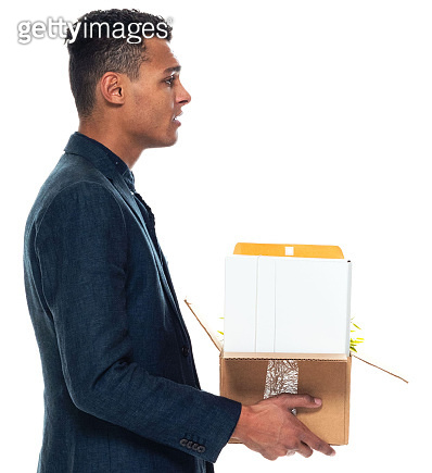 African-american ethnicity young male businessman standing in front of white background wearing businesswear and holding cardboard box