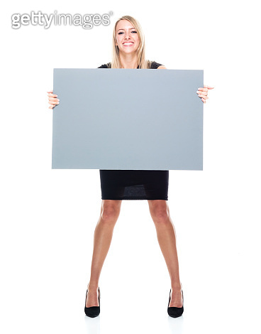 Caucasian female businesswoman standing in front of white background wearing businesswear and holding banner sign