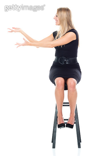 Caucasian female presenter sitting in front of white background wearing businesswear