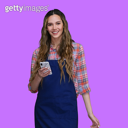 Caucasian female in front of in front of purple background wearing apron and using mobile phone
