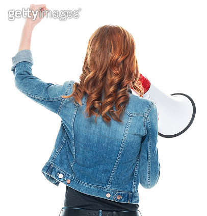 Caucasian young women in front of white background wearing pants and holding megaphone