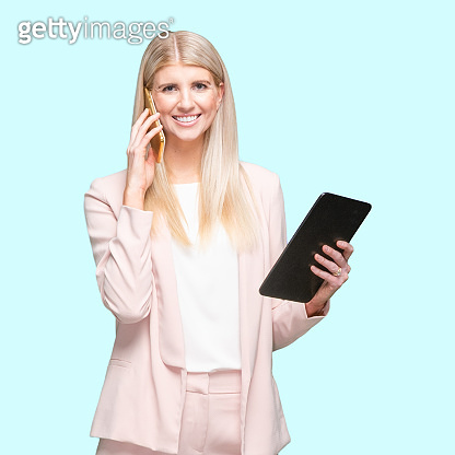 Caucasian young women business person standing in front of blue background wearing businesswear and using digital tablet