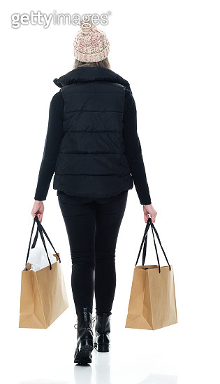 Caucasian young women shopaholic walking in front of white background wearing pants and holding bag