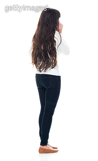 Latin american and hispanic ethnicity young women standing in front of white background wearing jeans and using mobile phone