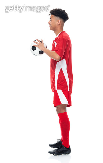 Generation z male athlete standing in front of white background wearing soccer uniform and holding soccer ball and playing soccer - sport and using sports ball