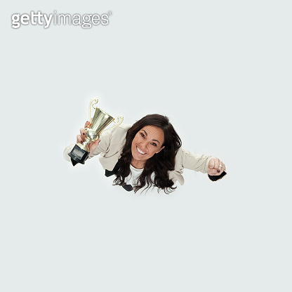 Caucasian mid adult women business person standing in front of white background in the office wearing businesswear and holding trophy
