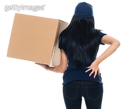 Latin american and hispanic ethnicity female manual worker standing in front of white background wearing polo shirt and holding package