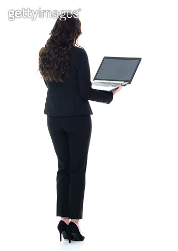 Caucasian young women business person standing wearing businesswear and using laptop