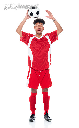 African-american ethnicity young male athlete standing in front of white background wearing soccer uniform and holding soccer ball and playing soccer - sport and using sports ball