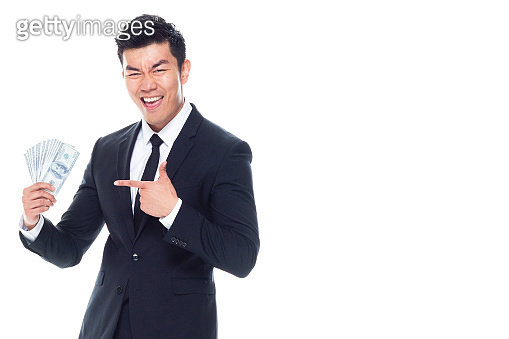 Chinese ethnicity male businessman standing in front of white background wearing necktie and holding currency