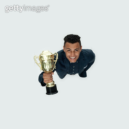 African-american ethnicity young male businessman standing in front of white background wearing smart casual and holding trophy