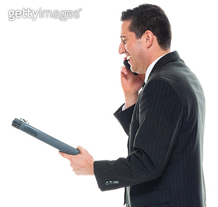 Caucasian young male manager standing in front of white background wearing businesswear and holding document and using mobile phone