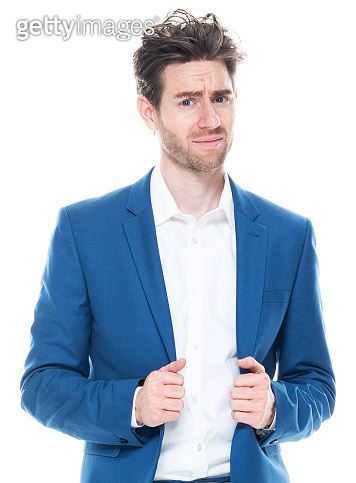 Caucasian young male businessman standing in front of white background wearing businesswear