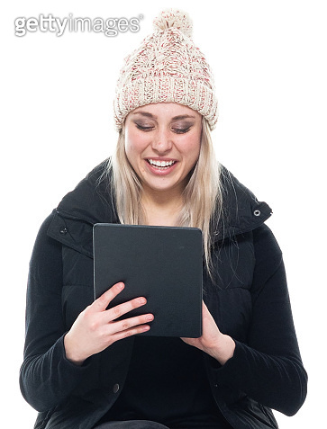 Caucasian female sleeveless crouching wearing warm clothing and using touch screen
