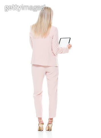 Caucasian female businesswoman standing wearing smart casual and using digital tablet