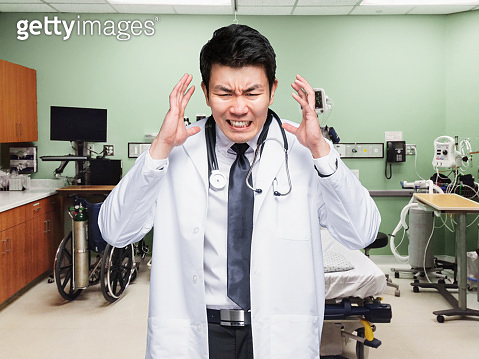 Chinese ethnicity male emergency services occupation standing at the hospital in the bedroom wearing lab coat