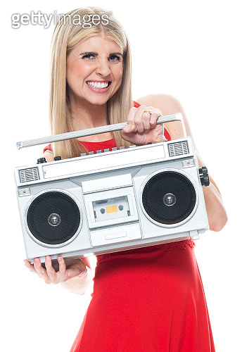 Caucasian female dancing in front of white background wearing dress and holding tape recorder