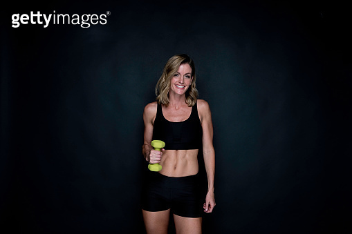Caucasian female exercising in front of black background wearing running shorts and being active with weight training