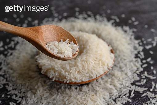 Milled rice in a bowl and a wooden spoon on the black cement floor. Selective focus