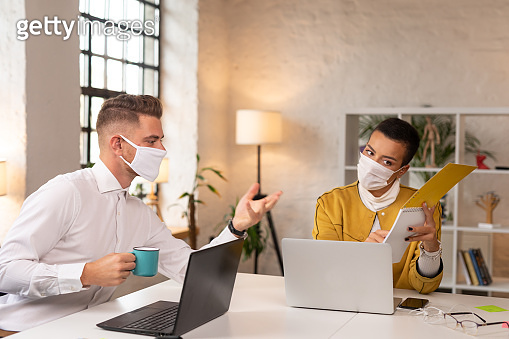 Young white collar workers discussing an assignment while wearing protective masks