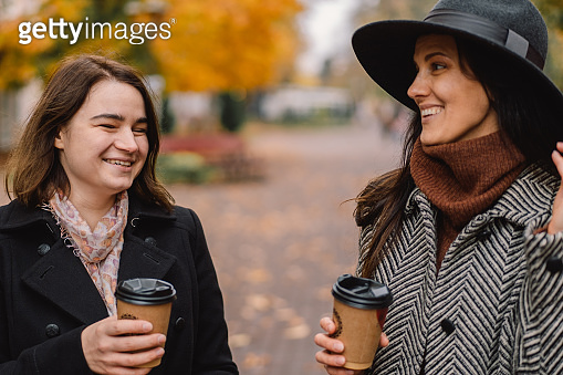 Girls drinking coffee in the park.