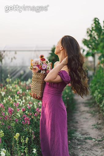 Portrait girl with long hair with a flower basket. Walk in the flower garden.