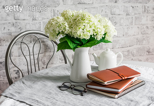 Bouquet of hydrangeas, notebooks, personal leather planner, white teapot on a table in a bright room. Cozy house concept