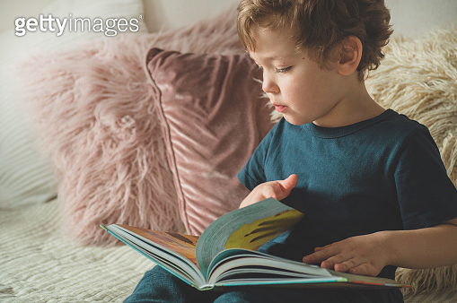 A little boy sits on a bed with your toys in living room watching pictures in story book