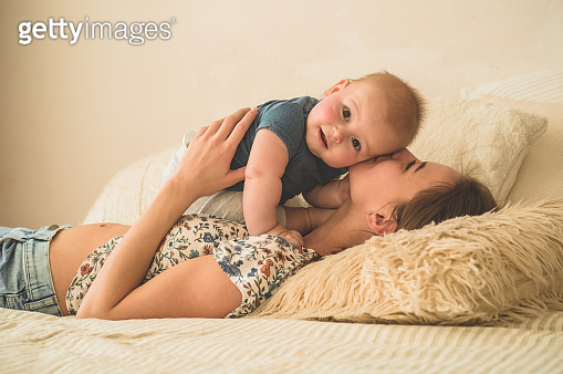 Love and family. Home portrait of a baby boy with mother on the bed. Mom play and kissing her child