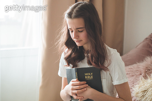 Christian teenage girl holds bible in her hands. Reading bible in a the living room. concept for faith, spirituality and religion